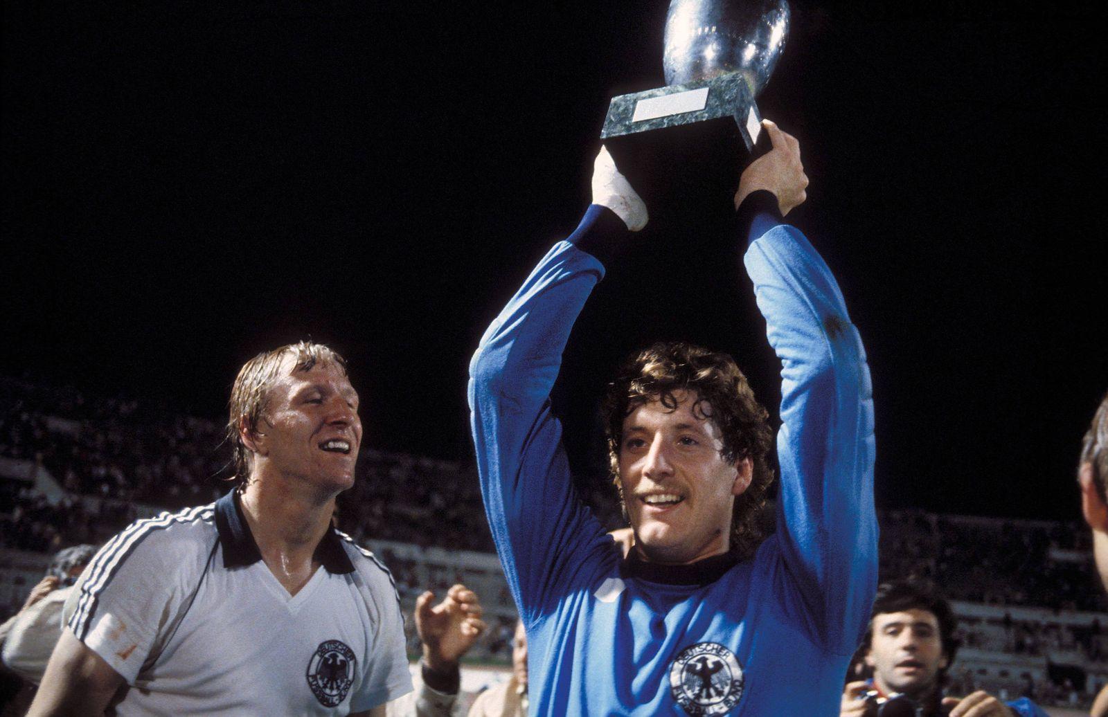 Torwart Harald Schumacher mit dem Europameister Pokal, bestaunt von Horst Hrubesch (beide BR Deutschland)