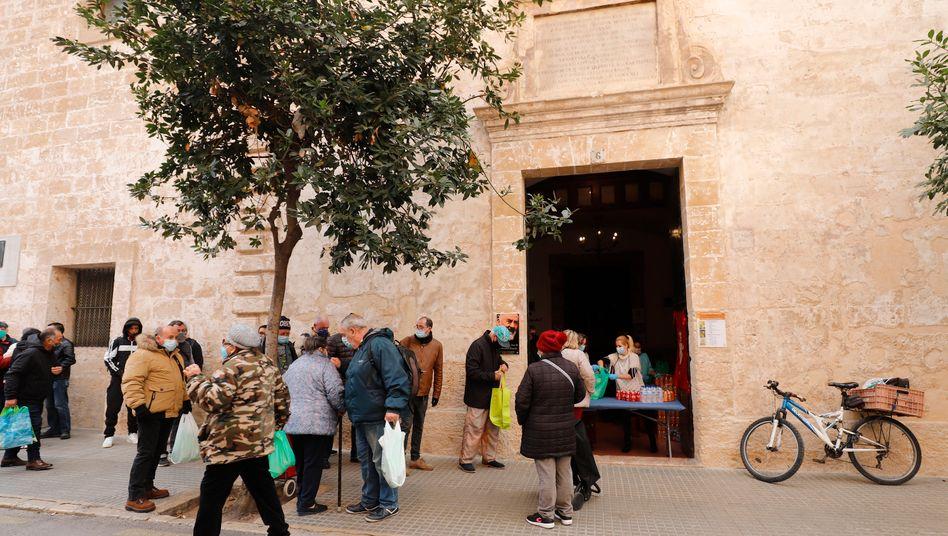 Menschen warten in einer Schlange, um ein Wohltätigkeits-Weihnachtsessen für arme und obdachlose Menschen in der Caputxins-Kirche in Palma de Mallorca zu bekommen (Foto von Dezember 2020)