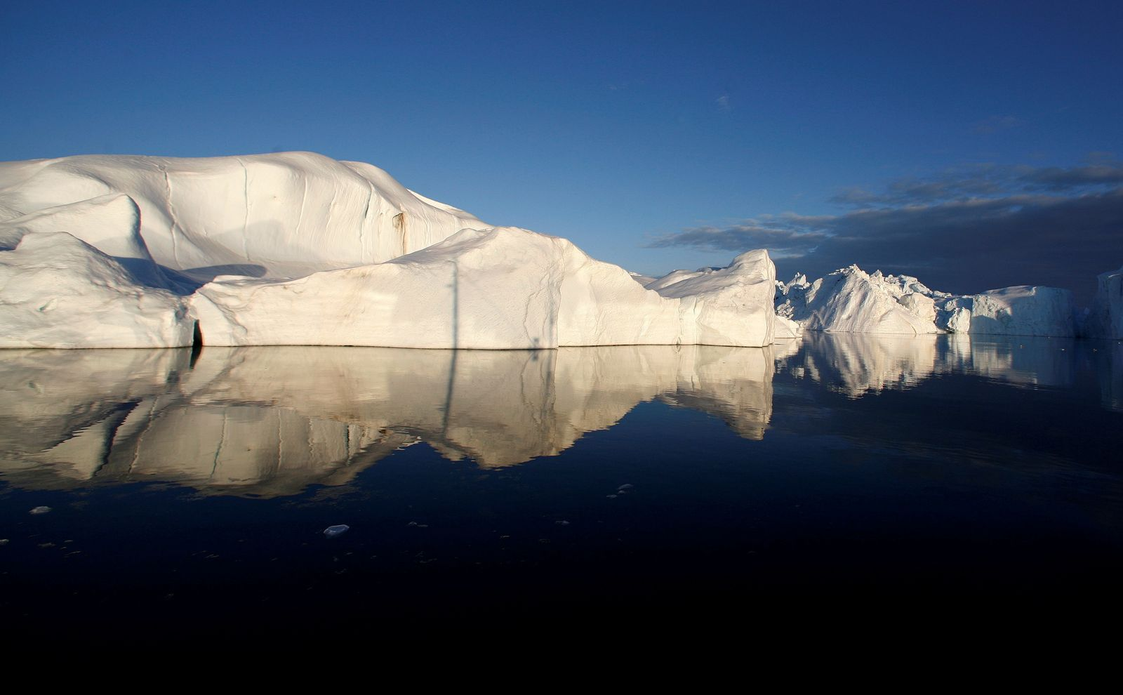 FILE PHOTO: Icebergs are reflected in the calm waters at the mouth of the Jakobshavn ice fjord near Ilulissat