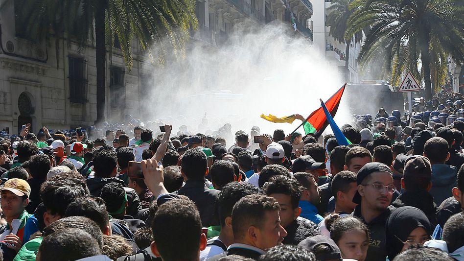 Demonstranten filmen den Einsatz von Wasserwerfern bei einem Protest gegen den algerischen Präsidenten Bouteflika und Algeriens Elite.