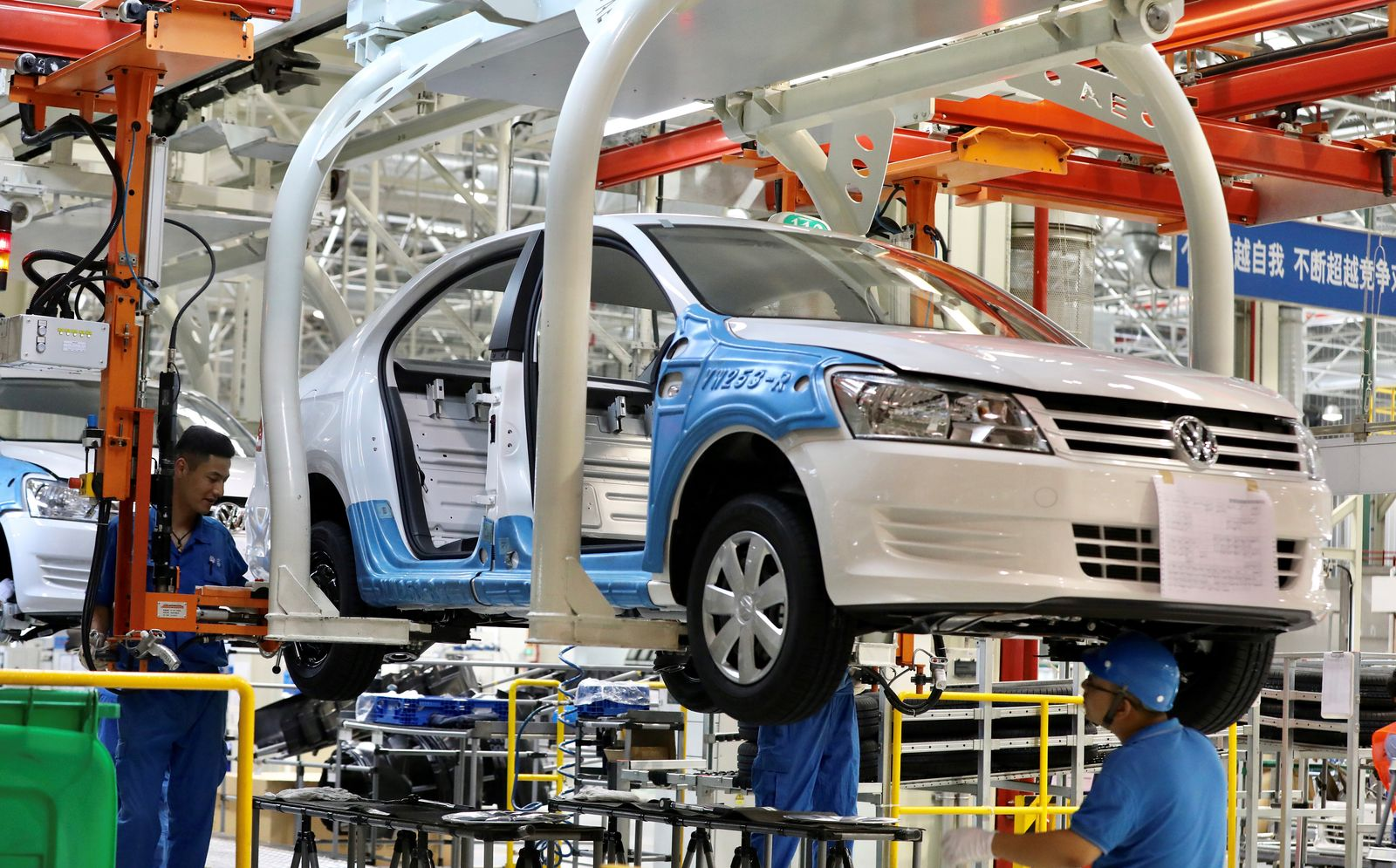 Employees work on assembling vehicles at a plant of SAIC Volkswagen in Urumqi, Xinjiang