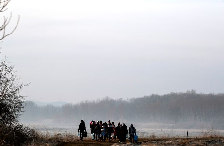 Migrants walking along the Evros River on their way into Greece from Turkey.