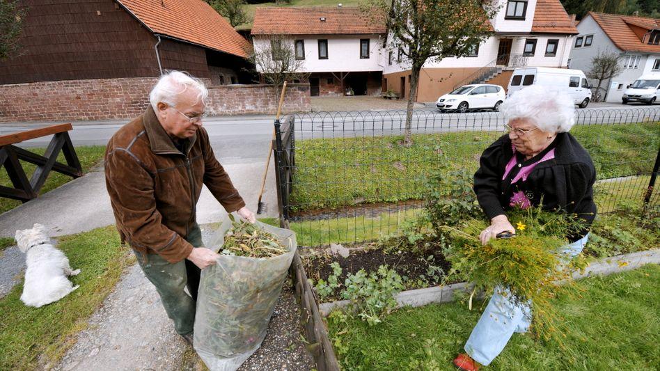 Rentnerpaar im eigenen Garten: Die Verrentung der Immobilie kann bei finanziellen Engpässen helfen