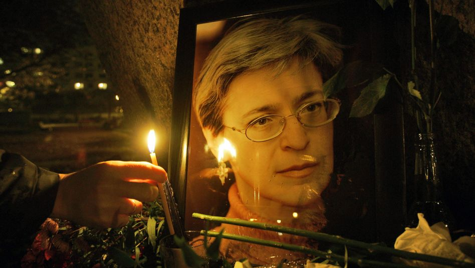 A mourner lights a candle for slain Russian journalist Anna Politkovskaya in 2006.