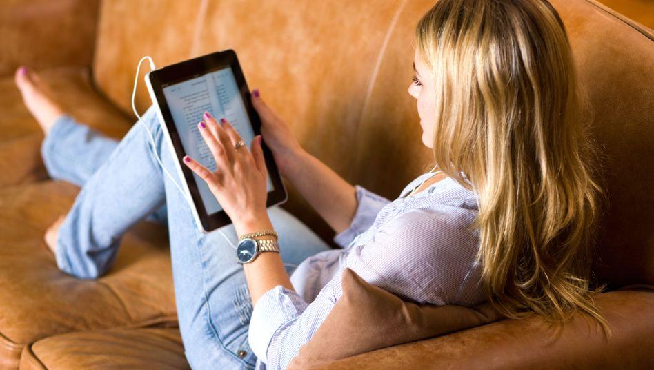 Tablet-Nutzung: Zu Hause auf dem Sofa Nachrichten konsumieren