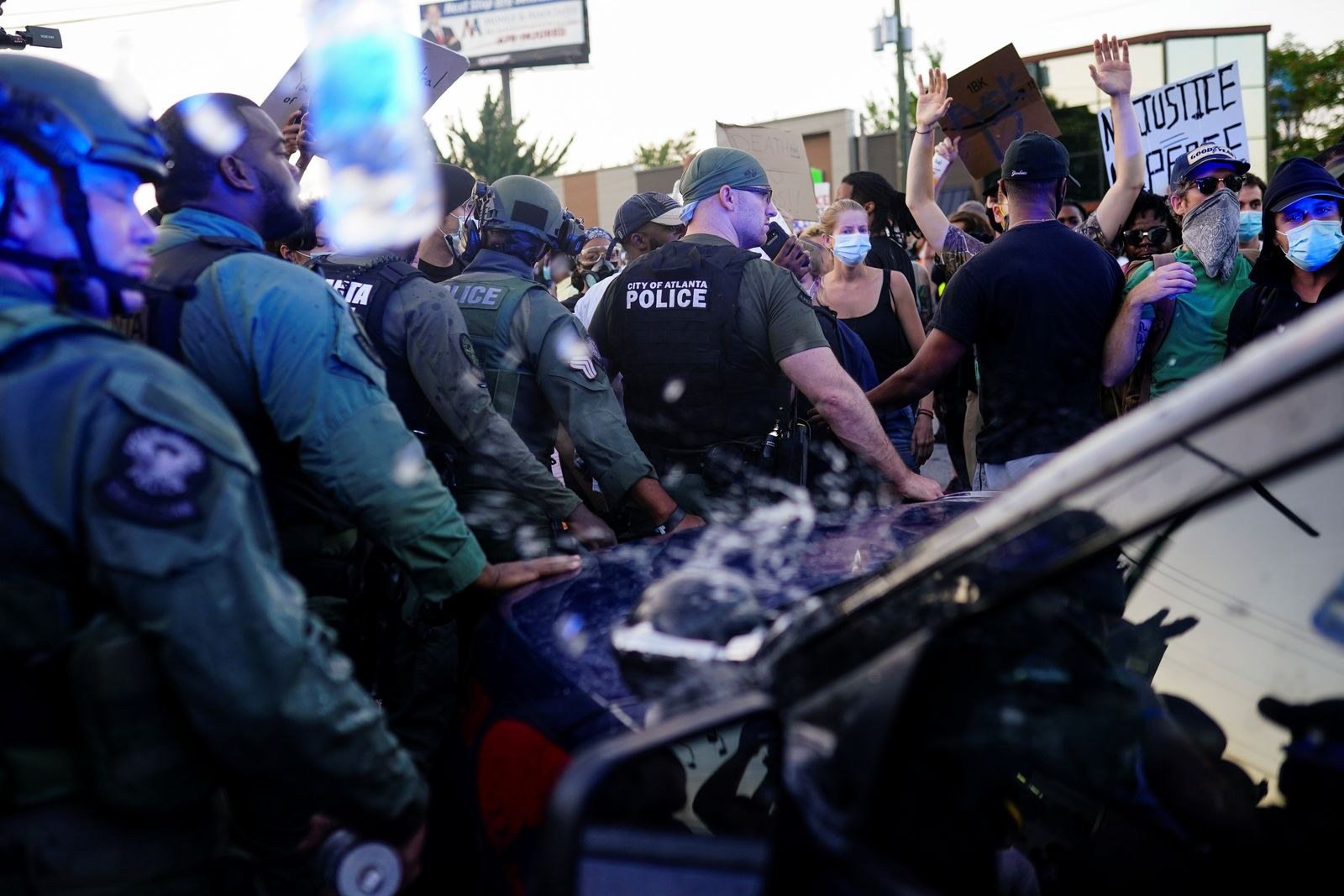 Police officers escort a police SUV from a crowd of protesters while bottles of water are thrown at them during a rally against racial inequality and the police shooting death of Rayshard Brooks, in Atlanta