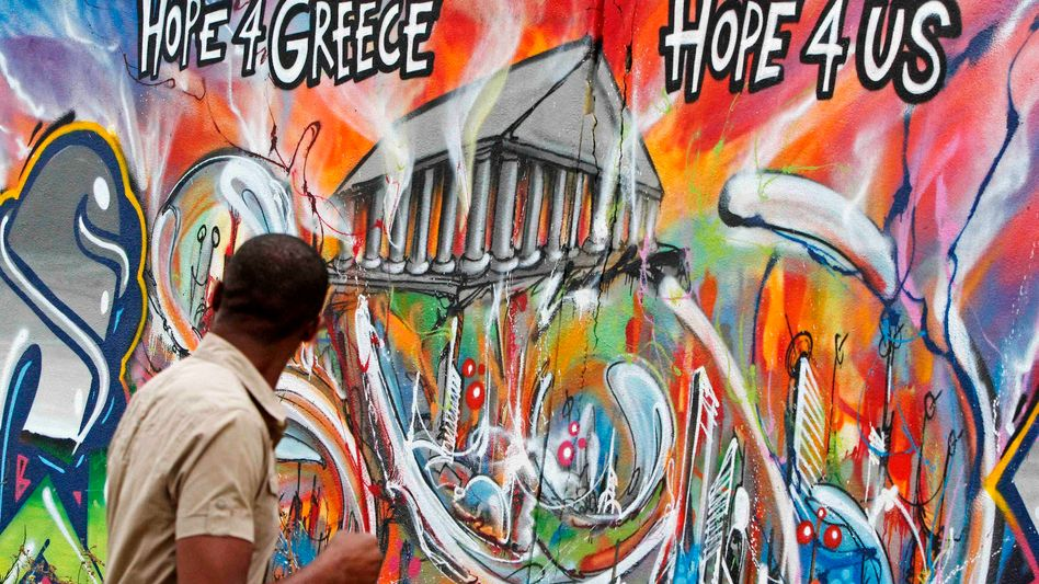 In Europe, all eyes are on Greece this Sunday. Here, a man walking past graffiti in Lisbon.