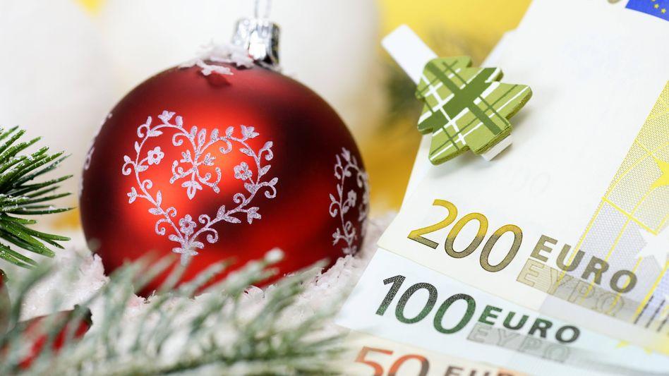 Weihnachtskugel und Geldscheine (Symbolbild)