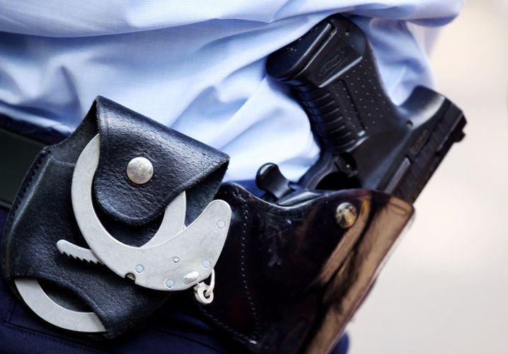 """Polizist mit Handschellen und Pistole (Archiv): """"Die Polizei ist schließlich für Sicherheit zuständig"""""""
