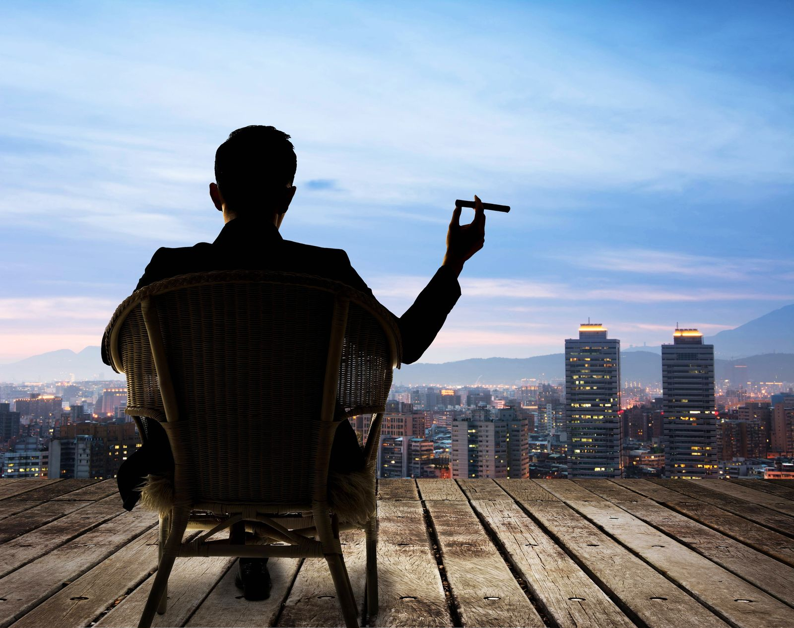 Silhouette of businessman sit on chair and hold a cigar and looking at the city in night model rele