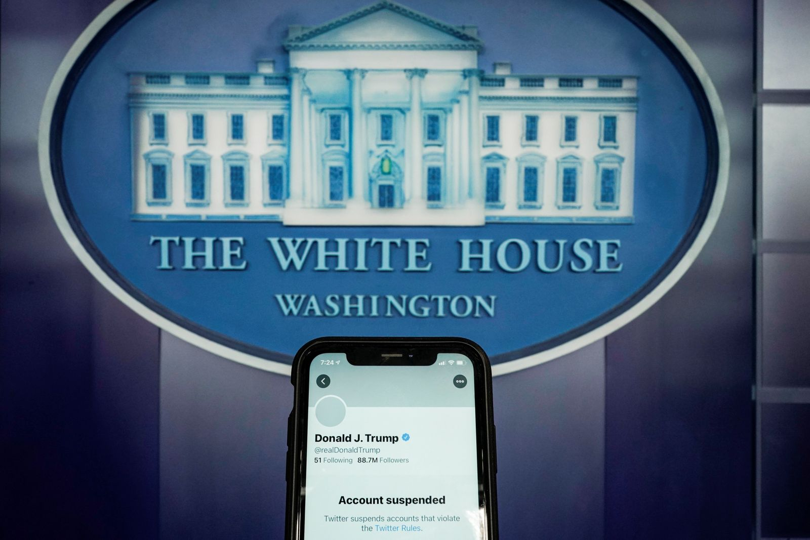 A photo illustration shows the suspended Twitter account of U.S. President Donald Trump on a smartphone at the White House briefing room in Washington
