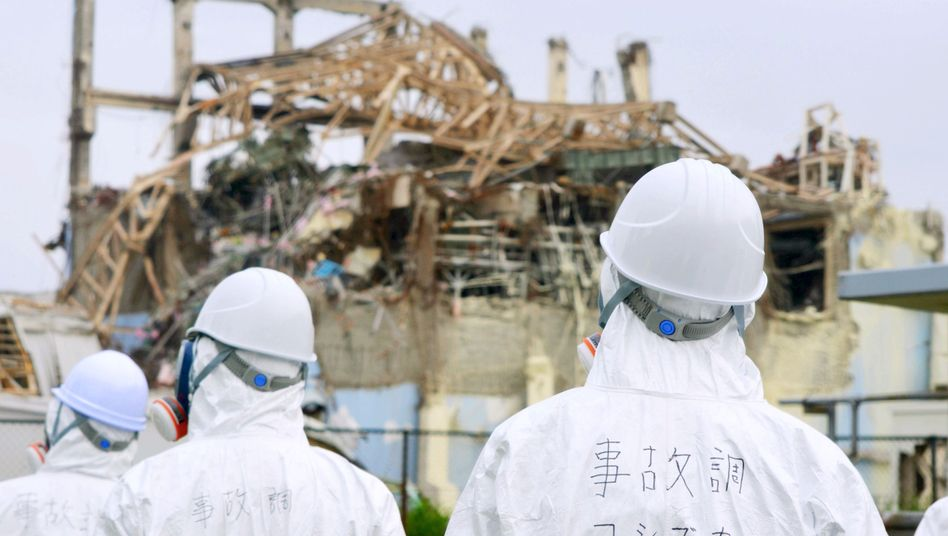 Japanese government inspectors looking at the damaged building housing reactor 3 at the Fukushima power plant.