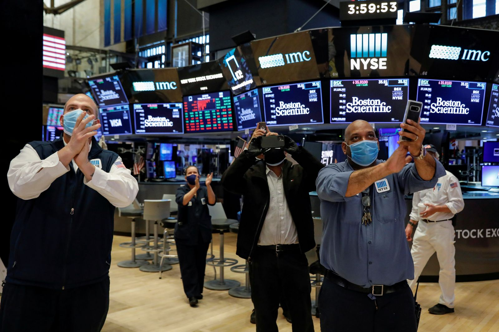 FILE PHOTO: Workers celebrate the during closing bell, as they prepare for the return to trading, on the floor at the NYSE in New York