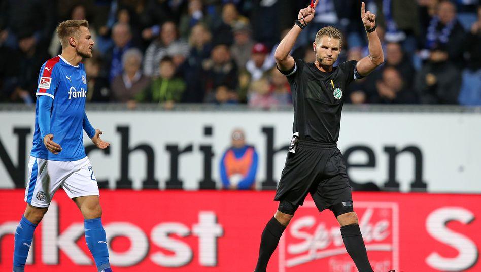 Schiedsrichter Timo Gerach (r.) zeigt den Einsatz den Videobeweises an, Kiels Jonas Meffert protestiert