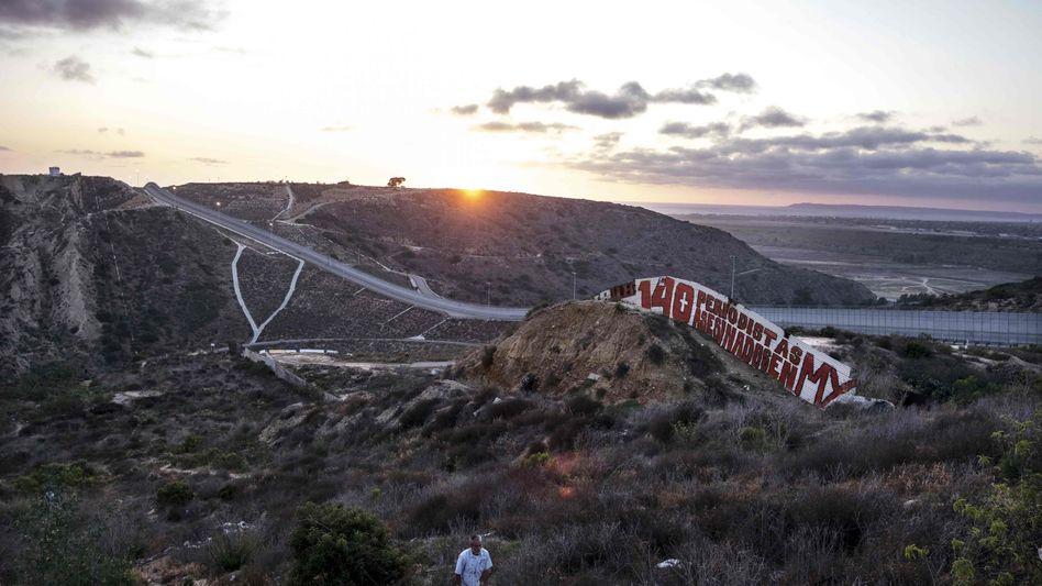 """Auf einer Mauer an der Grenze zwischen den USA und Mexiko steht """"140 Journalisten ermordet in Mexiko"""""""