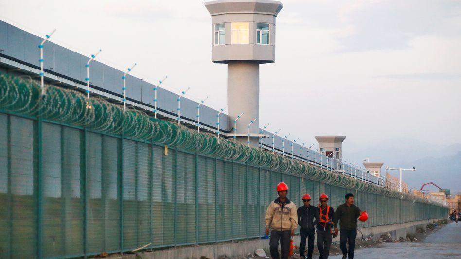 Arbeiter neben der Absperrung zu einem der sogenannten Berufsbildungslager in Xinjiang: Wer raus ist, ist noch lange nicht frei