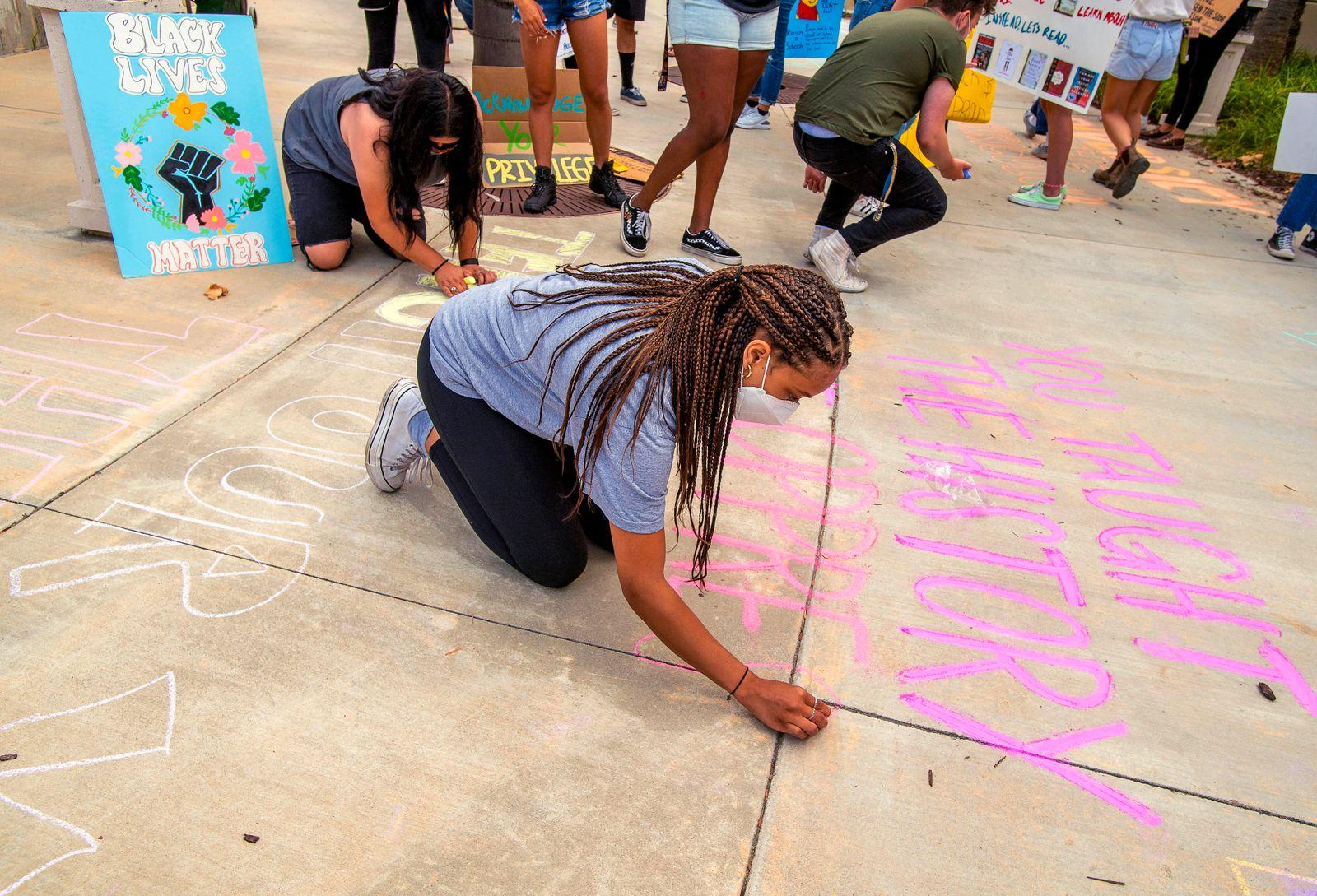 June 24, 2020, San Juan Capistrano, California, USA: Students write chalk messages outside the Capistrano Unified School