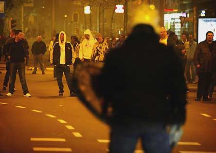 A Dutch policeman stands in front of hooligans during clashes between Dutch and Germans in the center of Rotterdam in 2002.