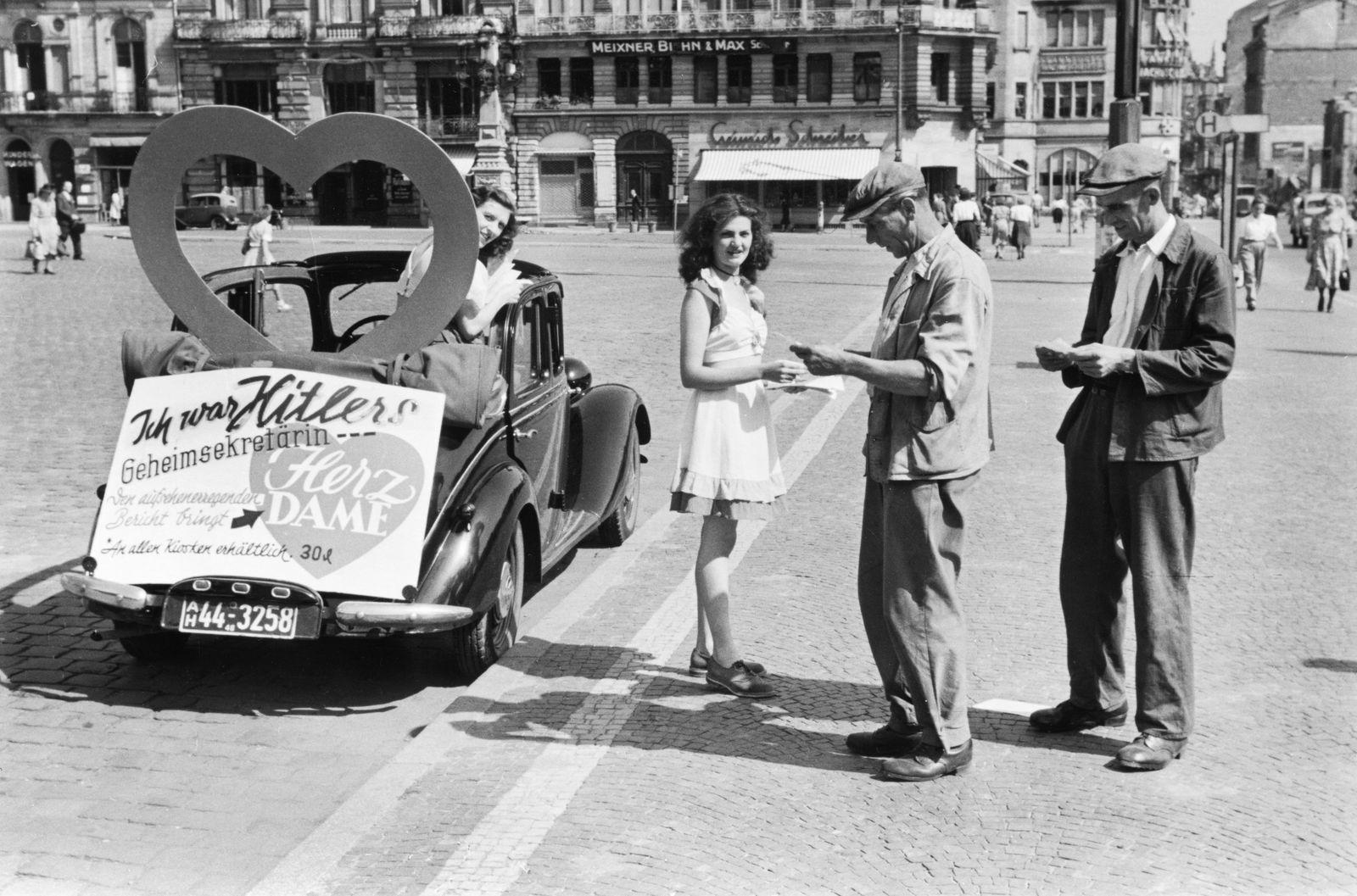 """Zwei junge Frauen machen Werbung für die Veröffentlichung des Berichtes """"Ich war Hitlers Geheimsekretärin"""""""