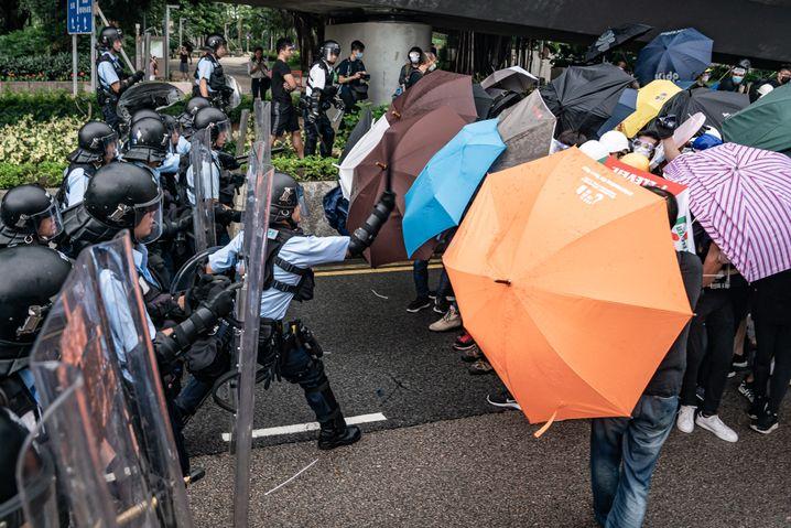 Angriff mit dem Knüppel: Ein Polizist schlägt auf Regenschirmdemonstranten ein