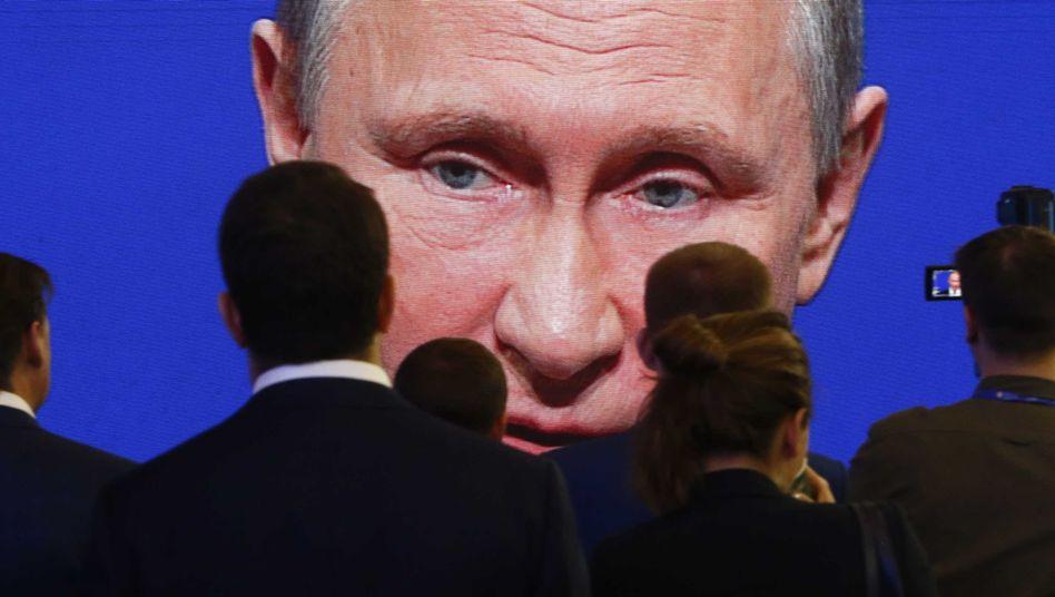 Teilnehmer des Internationalen Wirtschaftsforums in Sankt Petersburg verfolgen Wladimir Putins Rede