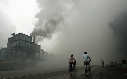 Cyclists pass through thick pollution from a factory in Yutian in China's northwest Hebei province. The Chinese government has forced the World Bank to remove embarrassing information about pollution deaths from a report, according to the Financial Times.