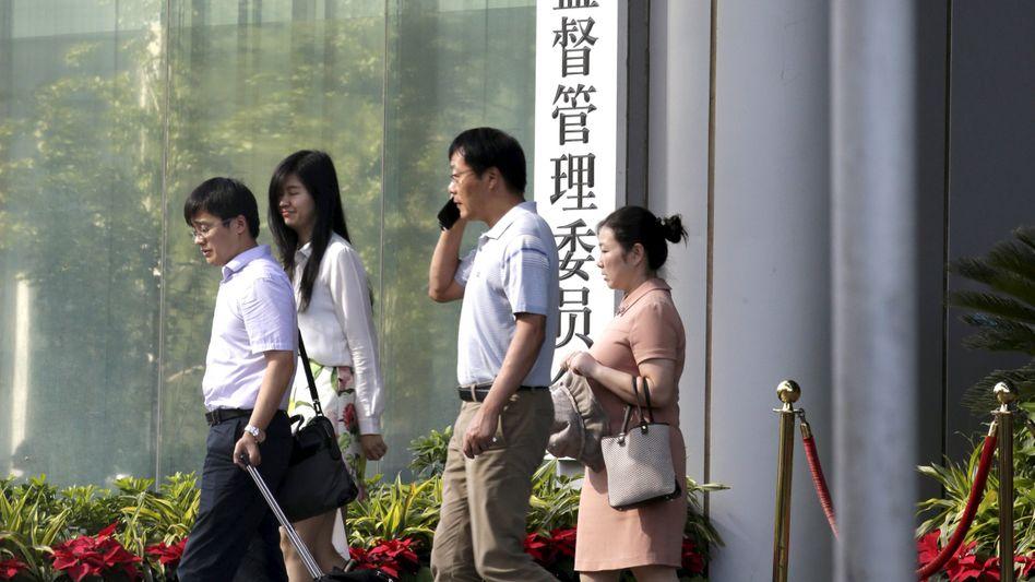 Passanten vor Schriftzug der chinesischen Behörde CSRC: Marktregulierung