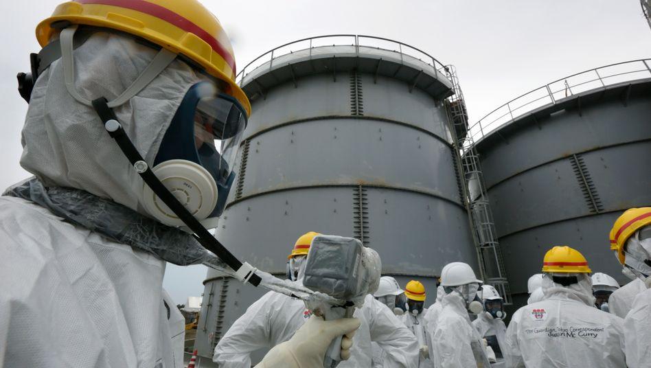 Mitarbeiter des Kraftwerkbetreibers Tepco messen Radioaktivität an Tank 4 des zerstörten AKW in Fukushima (Archivfoto)