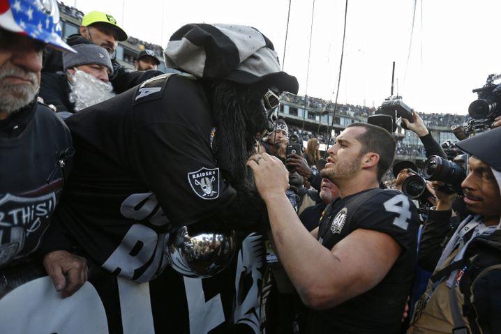 """Oaklands Quarterback Derek Carr spricht mit einem Fan aus dem """"Black Hole"""""""
