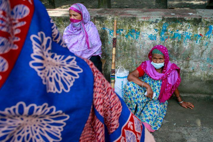 Frauen warten an einer Impfstelle auf dem Campus der Universität von Dhaka auf ihre Registrierung für die Corona-Schutzimpfung