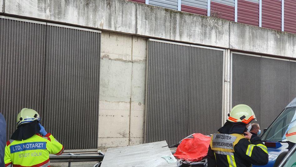 Einsatzkräfte am Unfallort: Das Betonteil stürzte auf das fahrende Auto