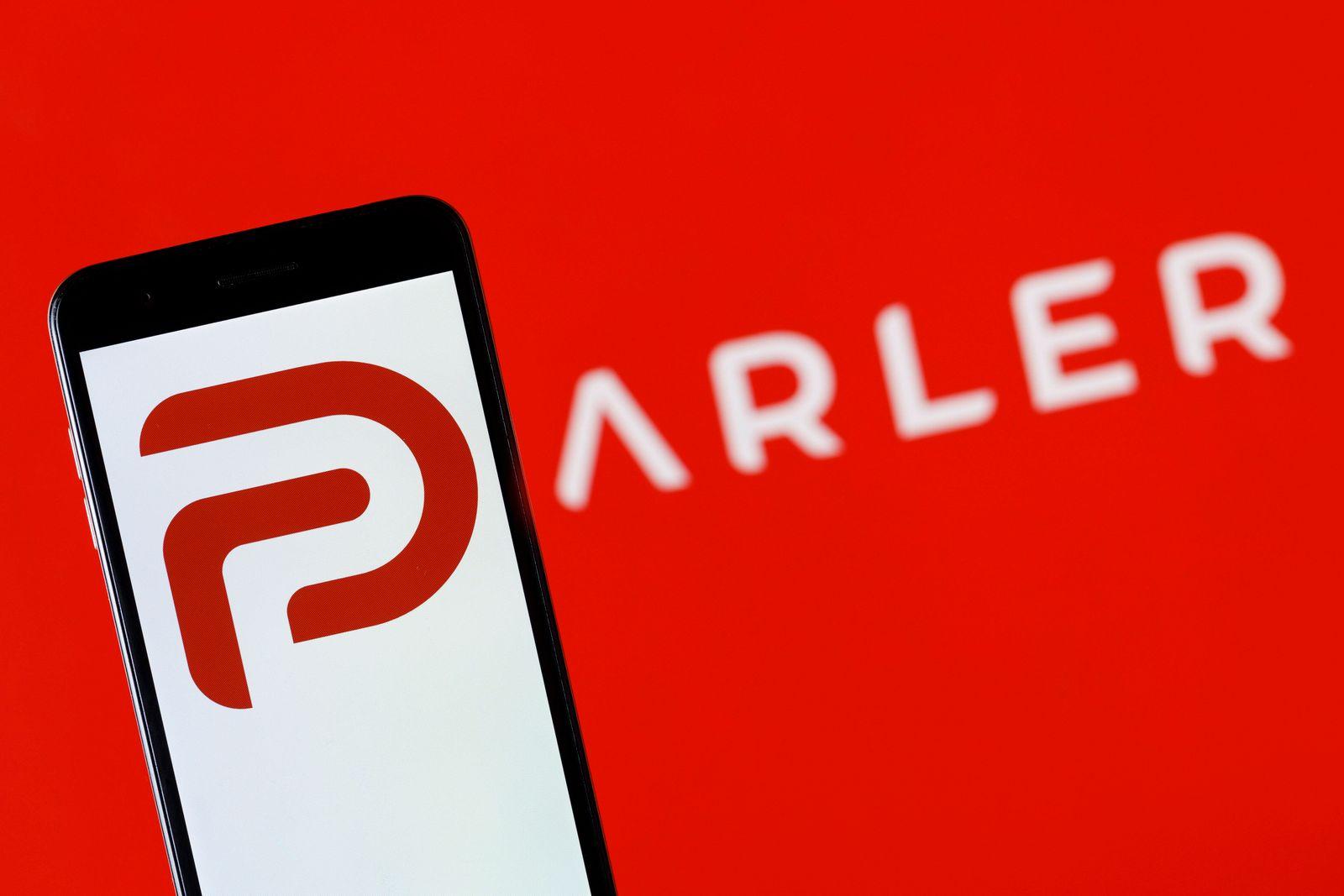 Parler-Logo auf einem Handy vor einem Bildschirm mit dem Parler-Schriftzug. Einen Tag nach Google haben auch Apple und