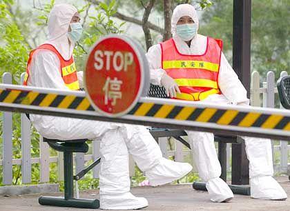 Vermummte Wächter bewachen den Eingang zu einem Quarantänelager in der Nähe von Hongkong