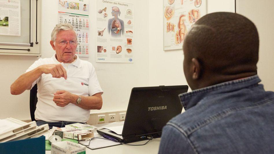 Mediziner Niebuhr (l.): Hilfe für einen Flüchtling aus Afrika