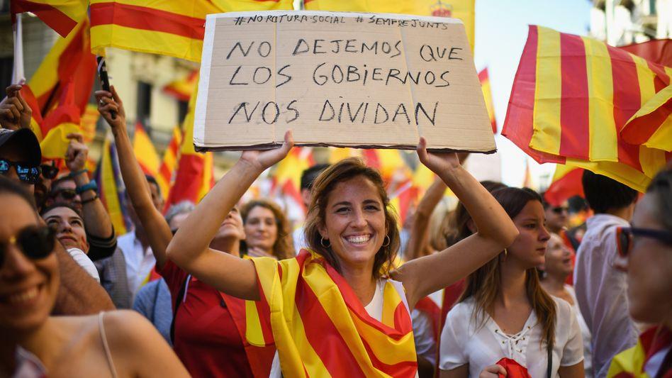 """Demonstrantin in Barcelona, auf dem Plakat steht """"Lassen wir uns nicht spalten von den Regierungen"""""""