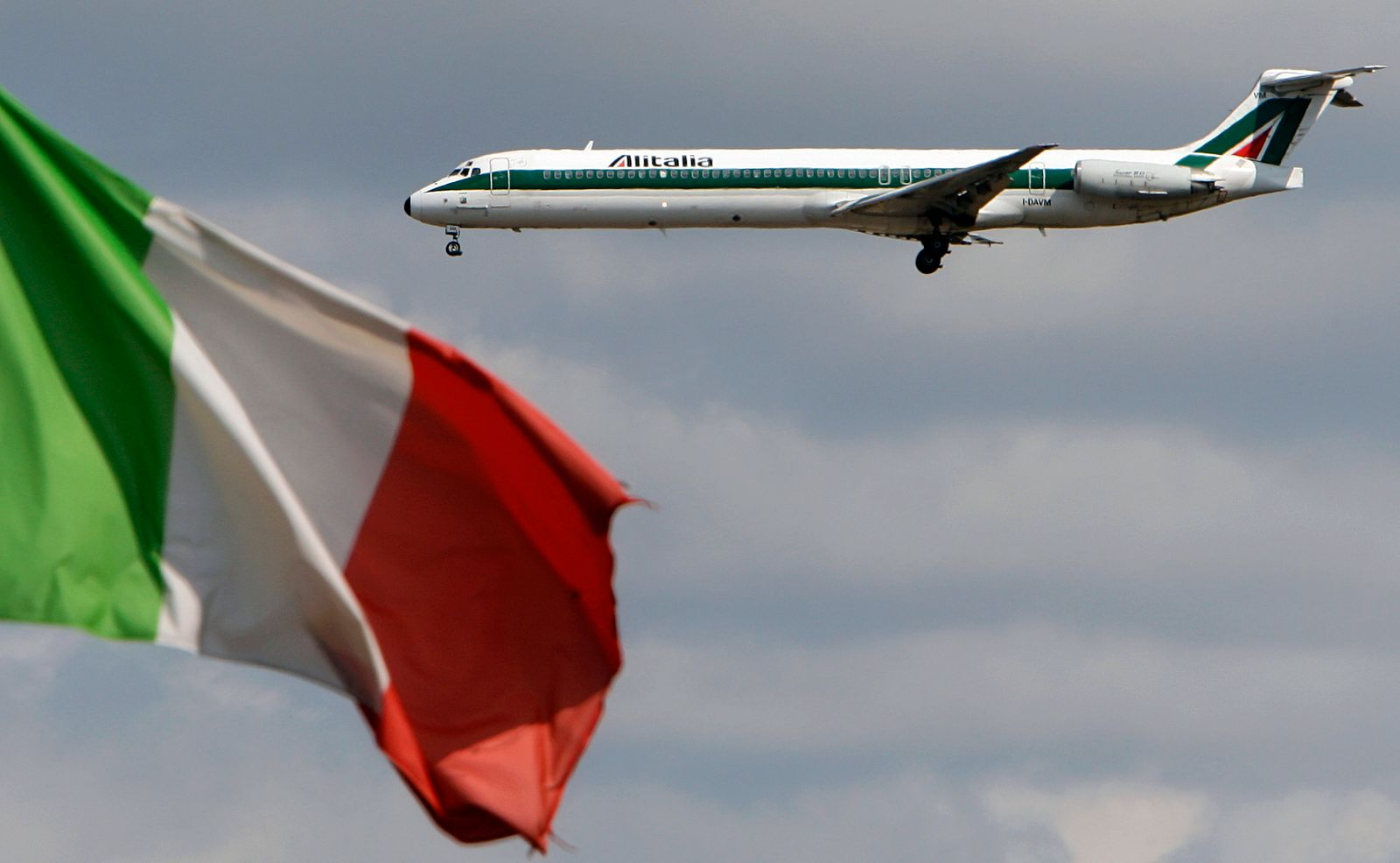File photo of an Alitalia plane approaching to land as an Italian flag is seen at Fiumicino international airport in Rome