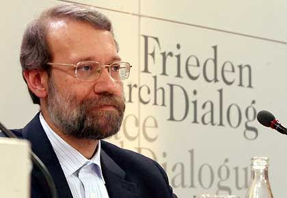 """Iran's nuclear negotiator Dr. Ali Larijani in Munich on Sunday. The text behind him reads """"Peace through Dialogue."""""""