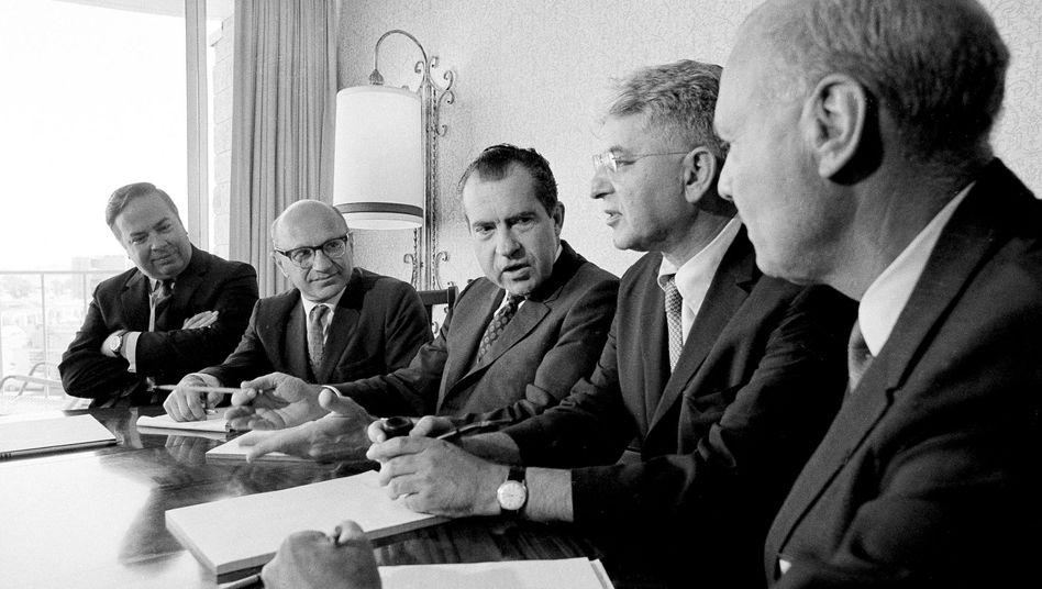 US-Präsident Richard Nixon (M.) umgeben von seinen Beratern Pierre A. Rinfret, Milton Friedman, Arthur Burns und Don Perlberg (v.l.)