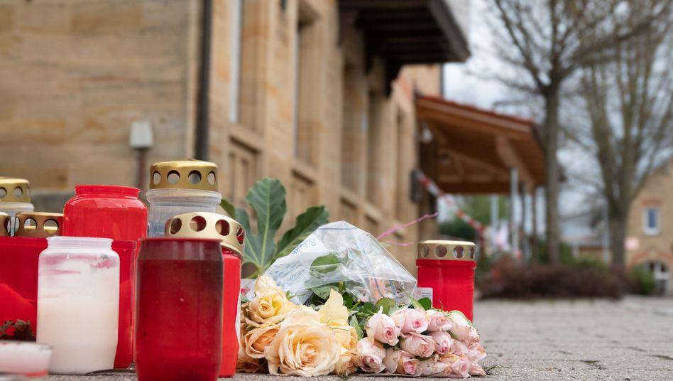 Rot am See: Vor einem Haus erinnern niedergelegte Rosen und Kerzen an die Bluttat.