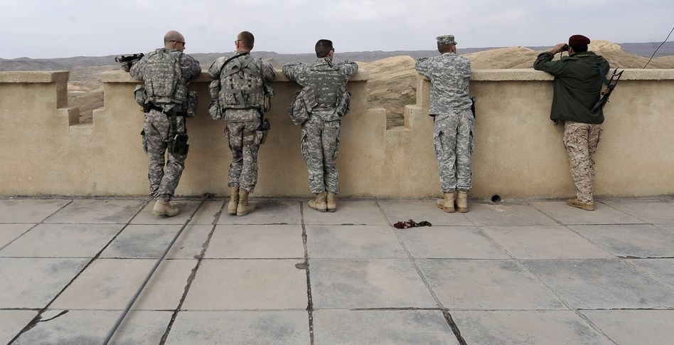 US and Iraqi soldiers peer over the border into Iran.