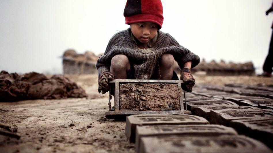 Ein vierjähriger Junge bereitet Ziegelsteine vor, bevor sie im Ofen gebrannt werden
