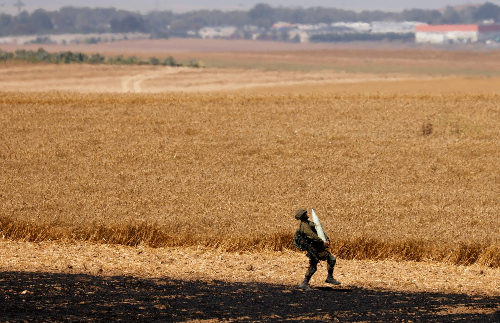 An Israeli soldier carries an artillery shell in a field near the border between Israel and the Gaza Strip, on its Israeli side