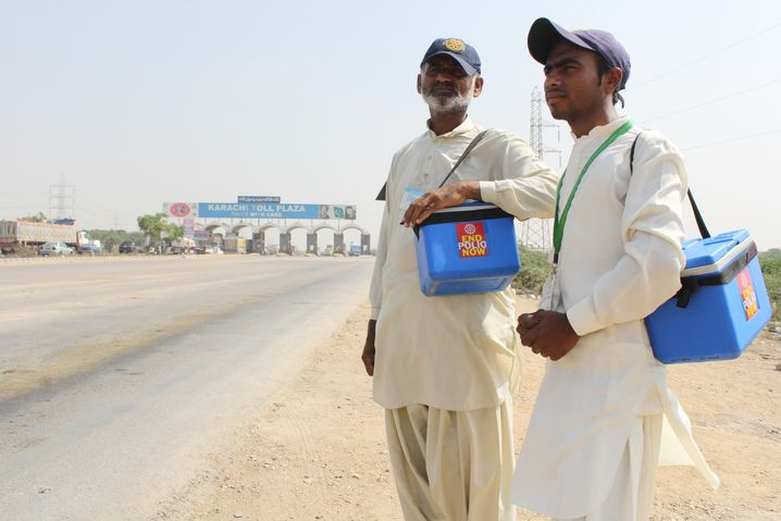 Zwei Impfhelfer am Rande des Karachi Toll Plaza - auch Kinder in vorbeifahrenden Bussen müssen auf Polioviren kontrolliert werden