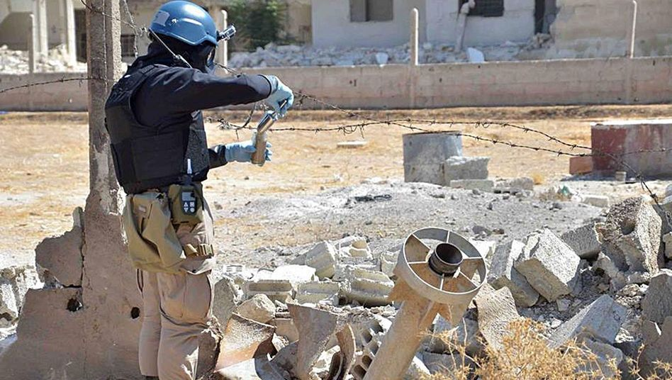A handout image purporting to show UN weapons inspectors collecting samples at the site of the Aug. 21 gas attack in Syria.