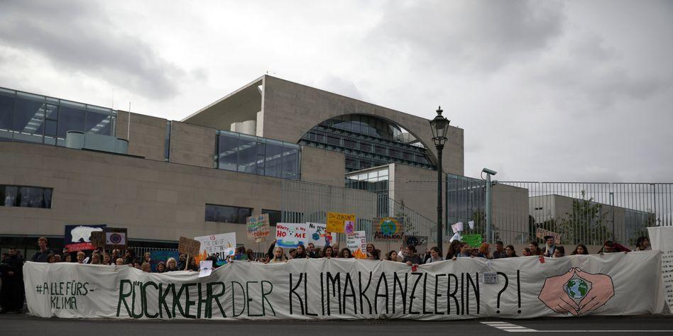 """Demonstranten halten ein Banner """"Rückkehr der Klimakanzlerin?!"""" beim Treffen des Koalitionsausschusses im Kanzleramt"""