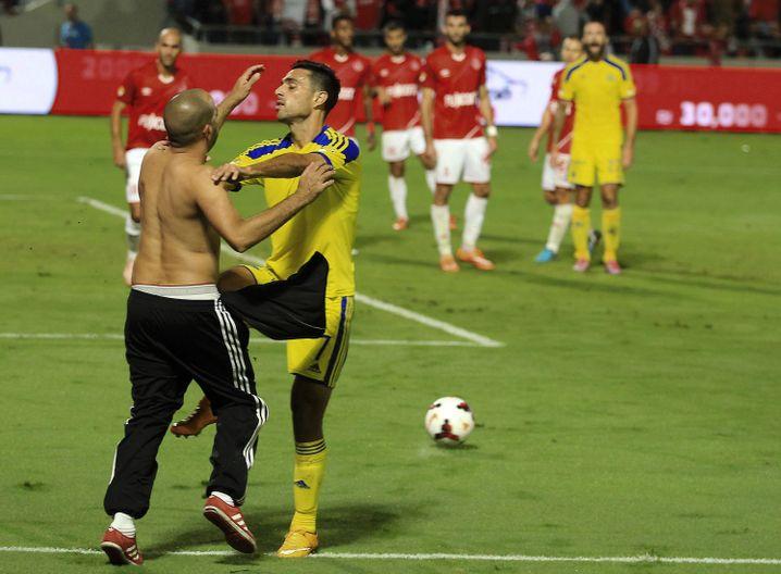 Ein Zuschauer stürmt beim Tel Aviver Derby das Feld und attackiert einen Maccabi-Profi. Das Foto entstand 2014
