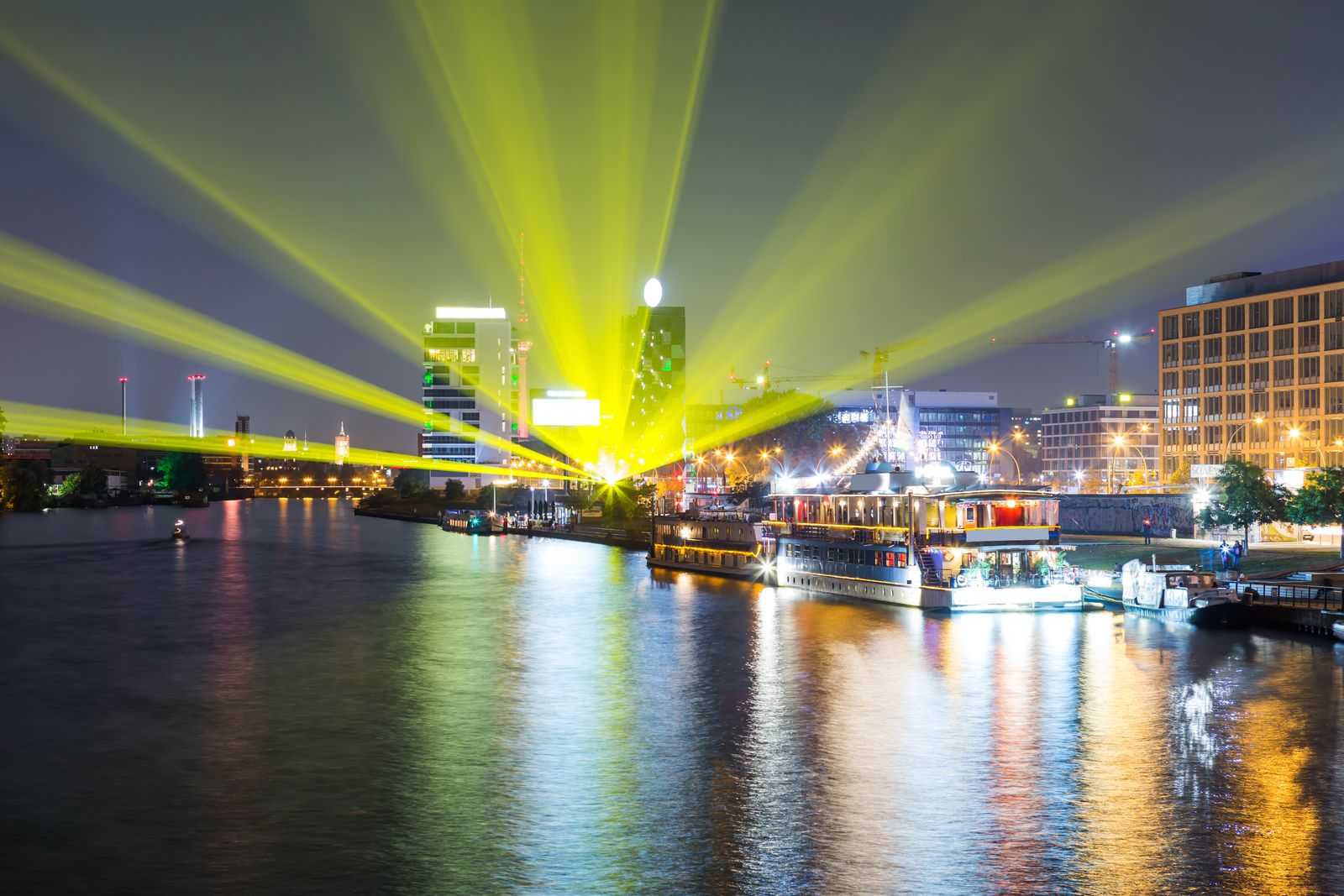 Yellow light beams in Berlin at Spree river