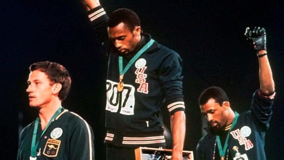 Der Protest von Tommie Smith (M.) und John Carlos (r.) bei den Spielen 1968 ging in die olympische Geschichte ein