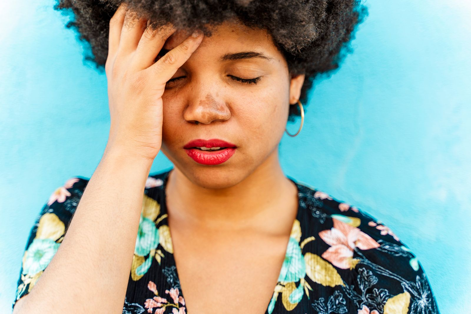 Portrait of Afro-American woman, hand on forehead, blue wall in the background model released Symbolfoto PUBLICATIONxINx