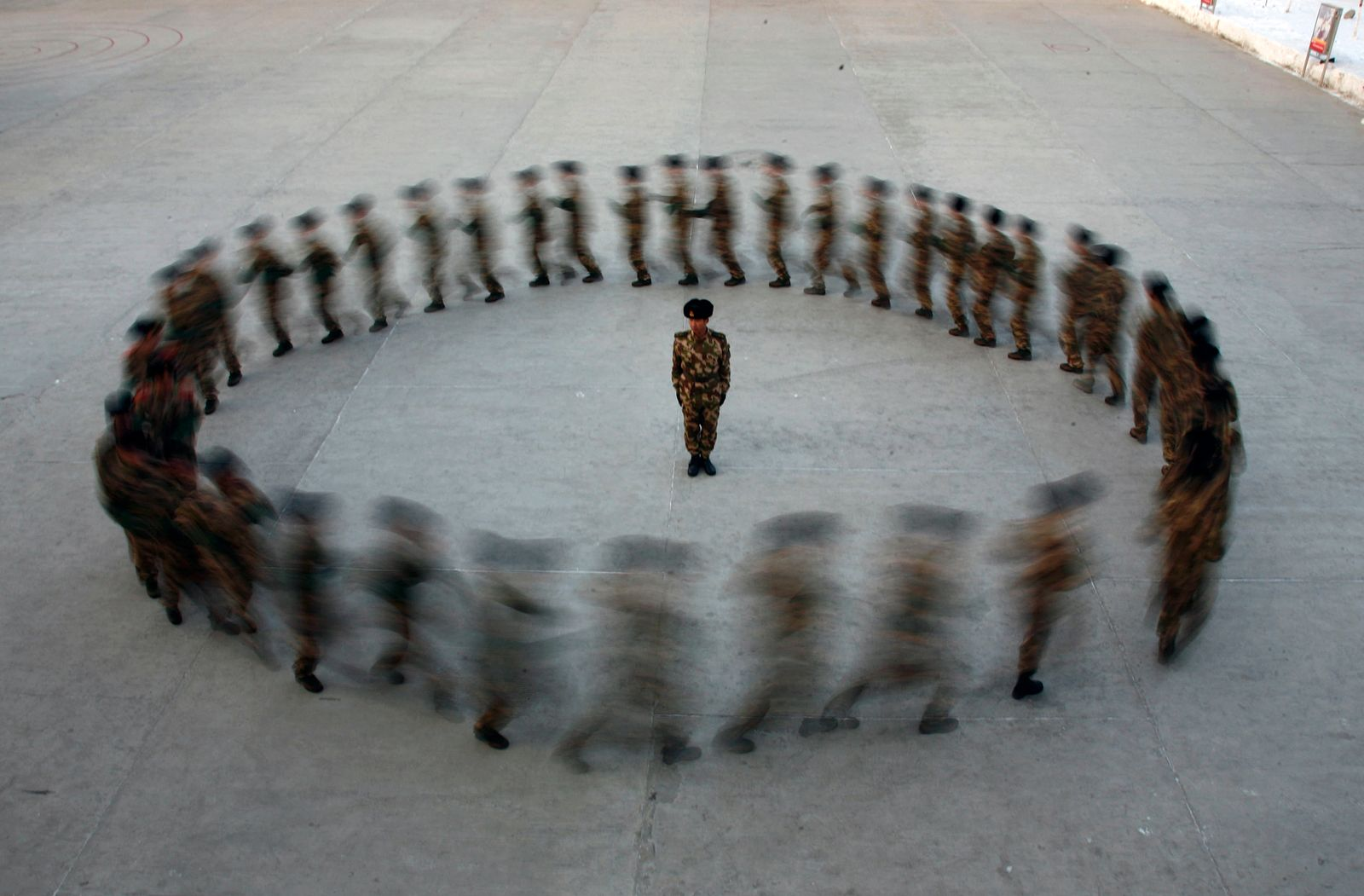 A commander watches as recruits of paramilitary police run in a circle during a training at a military base in Hami